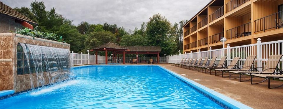 View Of The Outdoor Pool With Waterfall Feature At Best Western Ambador Inn And Suites